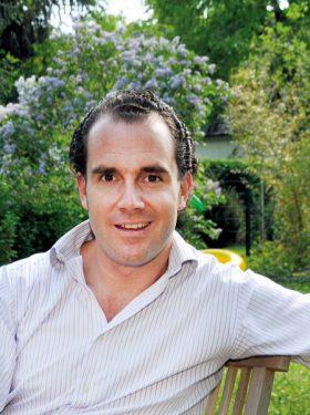 Dr. Dominik Pförringer auf einem stuhl in einem bepflanzten Garten